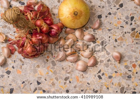 garlic, shallots, onion pile on marble floor - top viwe & copy space - stock photo