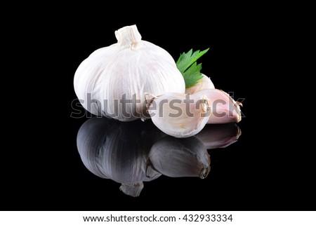Garlic with reflection on black background - stock photo