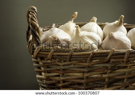 garlics in rustic wooden basket, dark background