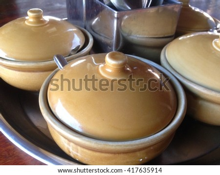 Garnish for noodles In ceramic cup on a brown wooden table. Flavoring  - stock photo