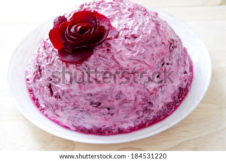 Garnish of beets with fish on white plate. - stock photo