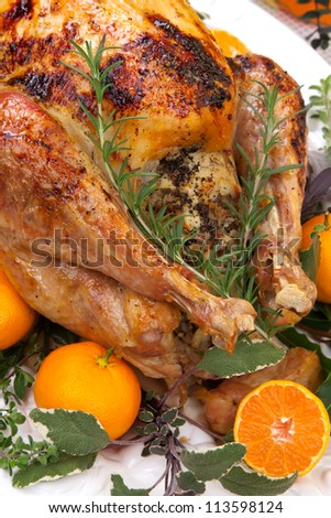 Garnished citrus glazed roasted turkey on holiday table, pumpkins, flowers, and white wine - stock photo