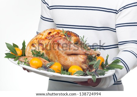 Garnished citrus glazed roasted turkey on platter is ready to be served