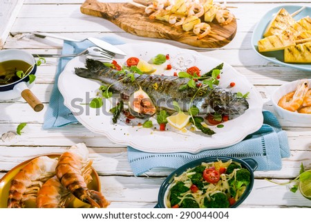 Garnished Grilled Whole Fish on White Platter on Rustic White Picnic Table Surrounded by Vegetable and Seafood Dishes and Blue Napkins - stock photo