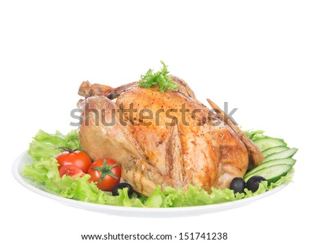 Garnished roasted thanksgiving chicken on a plate decorated with salad, olives, tomatoes, cucumbers isolated on a white background - stock photo