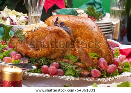 Garnished roasted turkey on Christmas decorated table with candles and flutes of champagne