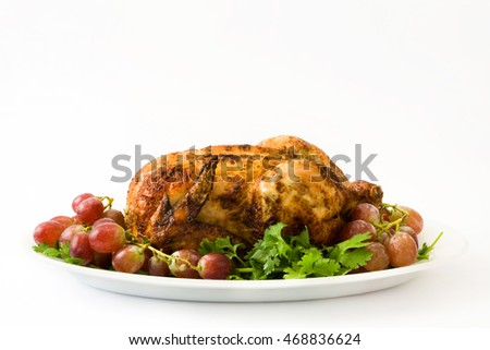 Garnished roasted turkey with grapes and herbs isolated on white background