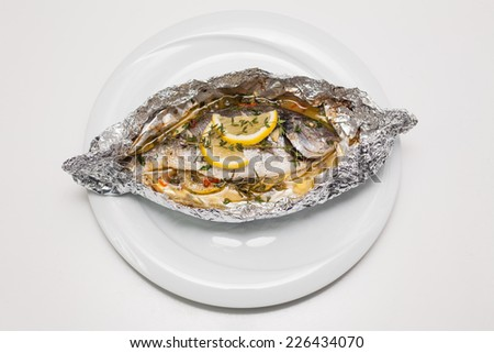 Garnished sea fish on plate with lemon