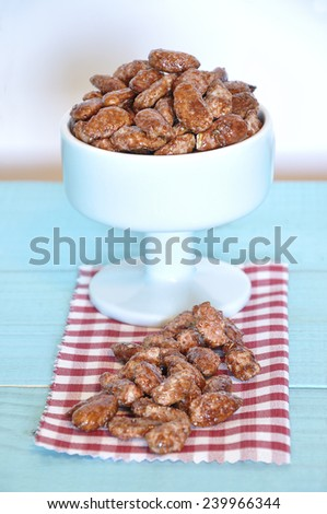Garrapinyades in a blue bowl on a red and white checkered napkin over an old wooden table. The Garrapinyades are nuts (usually almonds) coated with crunchy sugar. They are a typical of Spain. - stock photo