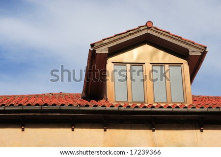 Garret in red tiled roof - stock photo