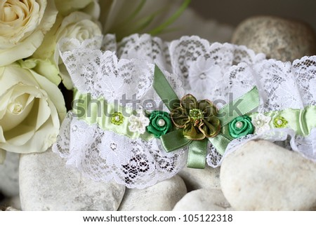 Garter in white lace with Green flower detail for bride displayed on white stone, white roses visible in corner. - stock photo