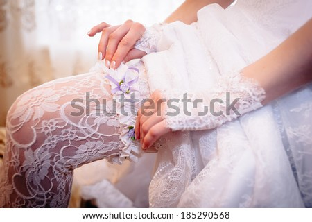 garter of bride. Legs of bride. beautiful bride in white wedding dress. Happy sexy girl waiting for groom. Romantic lady in bridal dress and flowers in hair have final preparation for wedding - stock photo