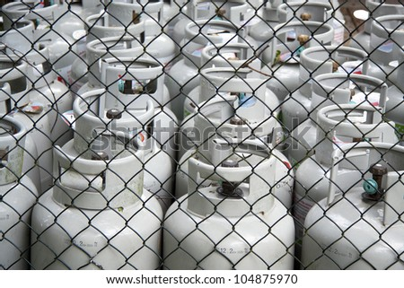 Gas bottles in a row behind a fence for background use - stock photo