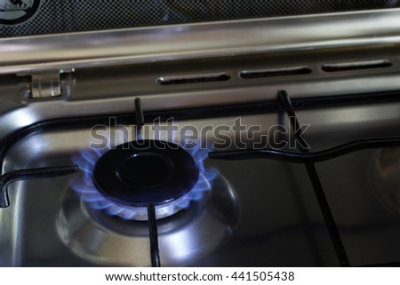 Gas burner on stove. Blue fire - stock photo