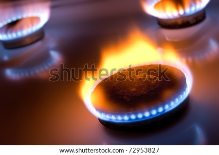 Gas burner with yellow flame in the kitchen oven - stock photo