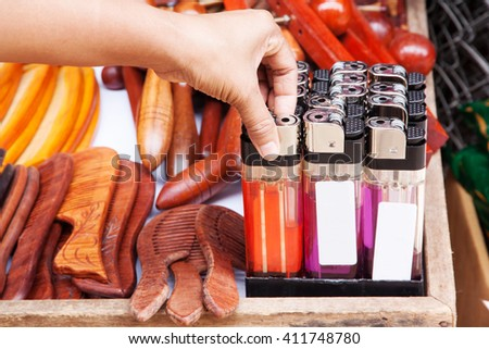 Gas Lighters multicolored it is large in tray. Compared to the hand. - stock photo