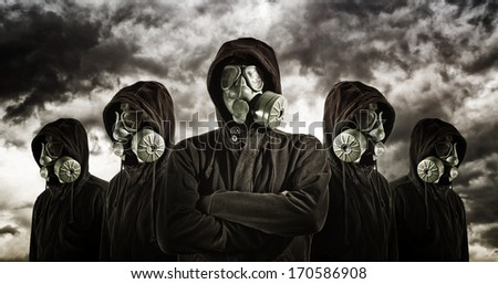 Gas mask soldiers over heavy storm clouds in background. - stock photo