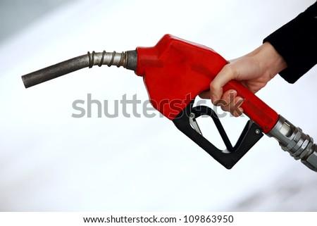 Gas nozzle in woman's hand - stock photo
