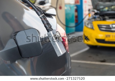 Gas nozzle to add gas in car at gas station - stock photo