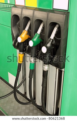 Gas nozzles at the gas station A row of 3 different gas pumps black yellow and green - stock photo