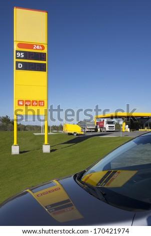 Gas, petrol station price post refection on car front window.