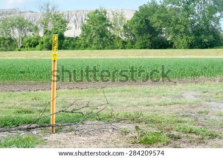 Gas Pipeline warning sign in front of young corn field with a mountain of quarry rock in the background - stock photo