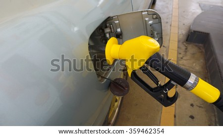 Gas pump nozzle in the fuel tank of a bronze car