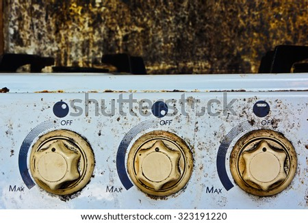 GAS RANGE THREE BUTTONS OF THE OLD WHITE STAINED GAS STOVE - stock photo