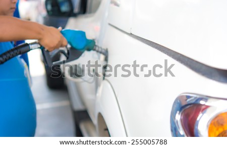 Gas station pump. Man filling gasoline fuel in car holding nozzle. Blur style . - stock photo