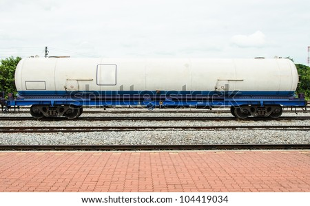 Gas tanker in freight train at station. - stock photo