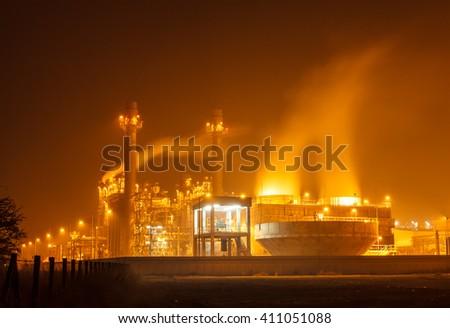 Gas turbine electrical power plant at dusk with orange sky - stock photo