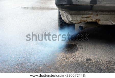 Gases emitted from the exhaust pipe dark old car, standing on the pavement. - stock photo