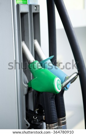 Gasoline nozzles for petrol and diesel at gas station - stock photo