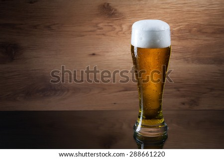 Gass of beer on wooden background with copyspace - stock photo