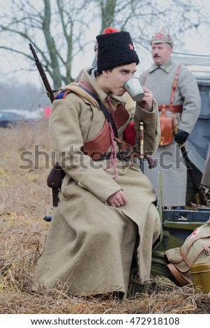 "GATCHINA, RUSSIA - NOVEMBER 07, 2015: Young soldiers of the Red Army is drinking tea from a tin cup. International military-historical festival ""the Civil war in Russia. North-West, 1919"""