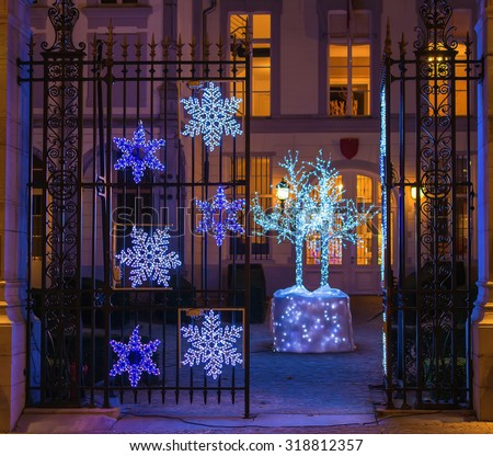 Gate decorated for Christmas and light tree in the front yard in Brussels, Belgium