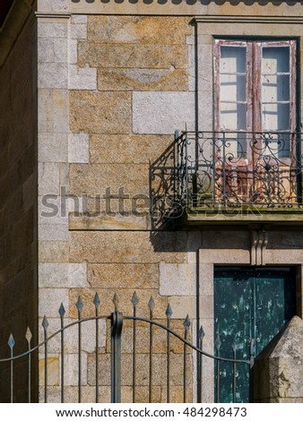 gate in front of old house with flowers on the balcony