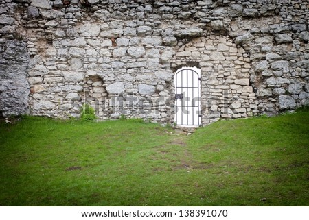 Gate in the old stone castle wall, architectural detail - stock photo