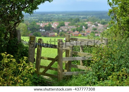 Gate or style overlooking typical English country village, Sussex