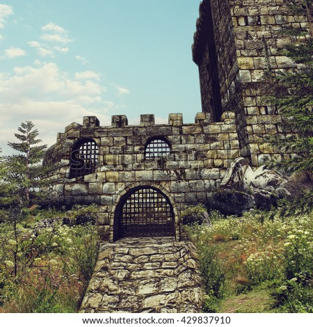 Gate to an old stone castle on a meadow. 3D illustration. - stock photo