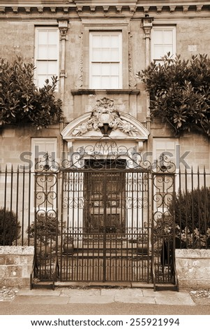 Gated Entrance and Front Door of an Attractive Old English Town House in Sepia - stock photo