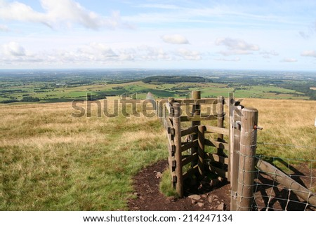 Gateway through a fence on Parlick Pike in the Lancashire Fells with Beacon Fell in the distance. - stock photo