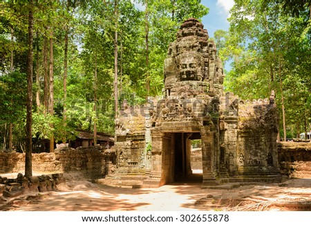Gateway to ancient Ta Som temple in amazing Angkor, Siem Reap, Cambodia. Gopura with stone face on woods background. Enigmatic Angkor is a popular tourist attraction.