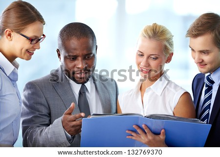 Gathered team of four making an important choice - stock photo