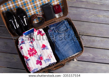 Gathering on vacation. Going on a business trip. Beautiful men's clothing in the suitcase of traveler. - stock photo