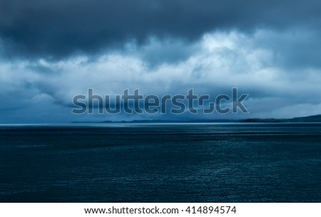 Gathering storm at dusk over an empty sea near Mull, Oban and Lismore, in the Inner Hebrides of Scotland. The mushroom shaped storm conveys loneliness, menace, and ominous and sullen feelings. - stock photo