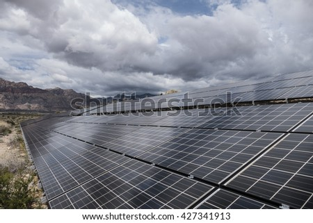 Gathering storm clouds over Mojave desert solar panels in Red Rock Canyon National Conservation Area near Las Vegas, Nevada.