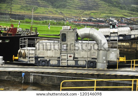 GATUN LOCKS - PANAMA CANAL-NOV. 7: Trains (mules) side Panama Canal.  These mules are used for side-to-side and braking control in the rather narrow locks On nov. 7 2012 in Panama. - stock photo