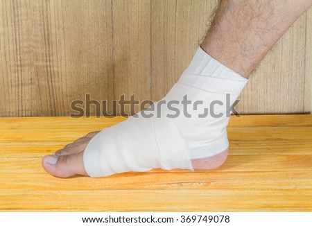 gauze bandage the foot treating patients ulcers male is wrapping his  injury  - stock photo