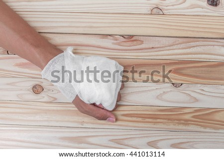gauze bandage the hand contusion treating patients with a wrist left  wrapping his injury on  wooden table background
